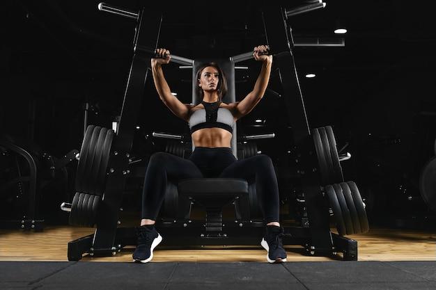 Szczupła, kulturystka, wykonuje ćwiczenia na ręce na siłowni.