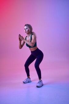 Szczupła lekkoatletka robi ćwiczenia w studio, neonowe tło. fitness sportsmenka na sesji zdjęciowej, koncepcja sportu, motywacja do aktywnego stylu życia