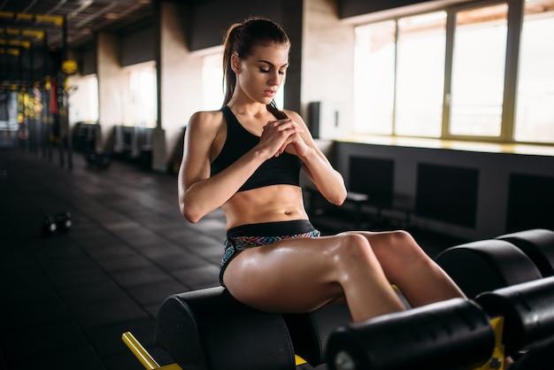 Szczupła lekkoatletka trenuje prasę w sportowej siłowni