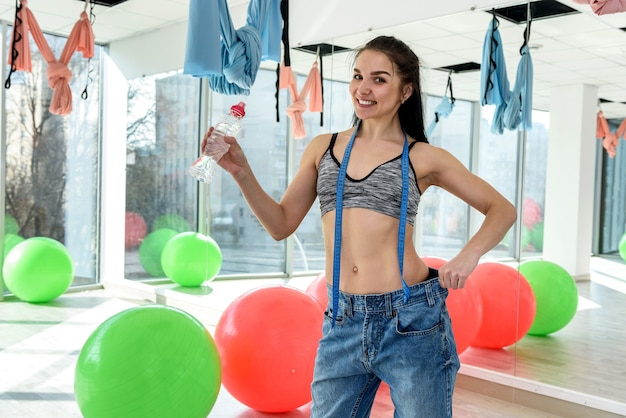 Szczupła młoda atrakcyjna kobieta z butelką wody i pokazuje wynik utraty wagi w klubie fitness lub na siłowni. zdrowy tryb życia