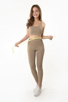 Szczupła młoda azjatycka kobieta mierzy jej ciało na bielu
