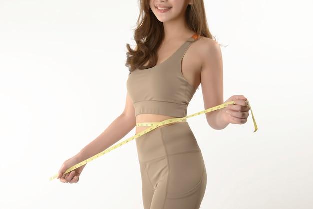 Szczupła młoda azjatycka kobieta mierzy jej ciało