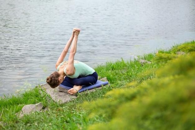 Szczupła młoda brunetka joga wykonuje trudne ćwiczenia jogi na zielonej trawie na tle przyrody