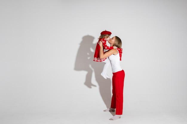 Szczupła młoda dama w czerwonych spodniach trzyma śliczną dziewczynkę i daje jej buziaka. koncepcja wakacje. skopiuj miejsce
