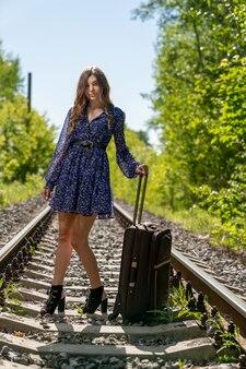 Szczupła, młoda dziewczyna w lekkiej sukience stoi na szynach, trzymając się długiej rączki podróżnej walizki