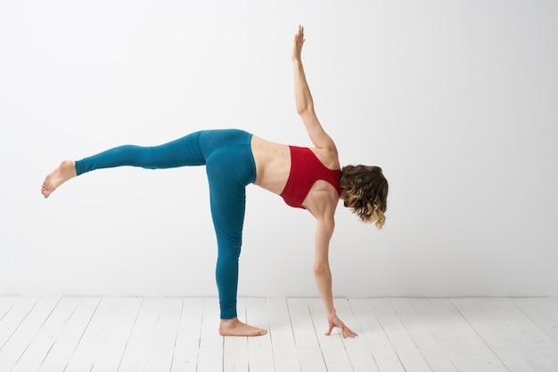 Szczupła młoda kobieta ćwiczy jogę i ćwiczy w domu