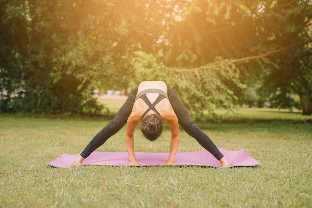 Szczupła młoda kobieta ćwiczy w ogródzie