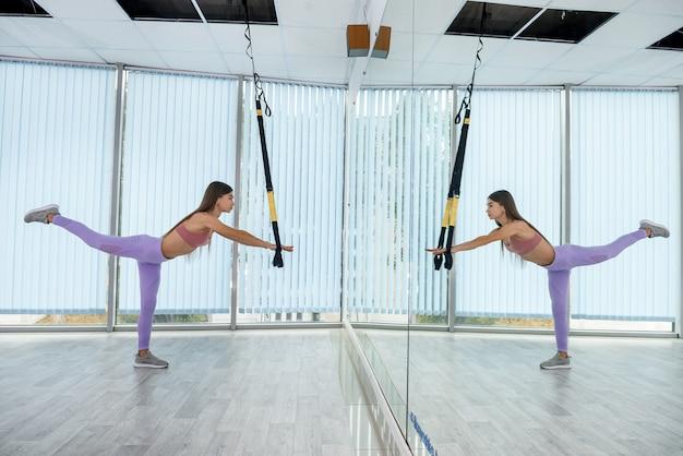 Szczupła młoda kobieta ćwiczy z paskami trx na siłowni. trening fitness dla kobiecego ciała
