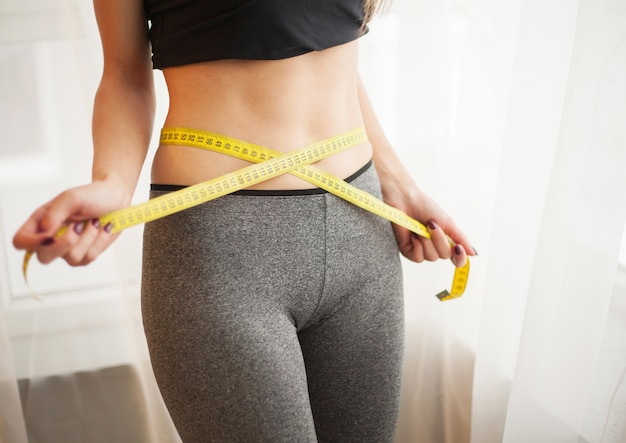 Szczupła młoda kobieta mierzy jej cienką talię z taśmy miarą