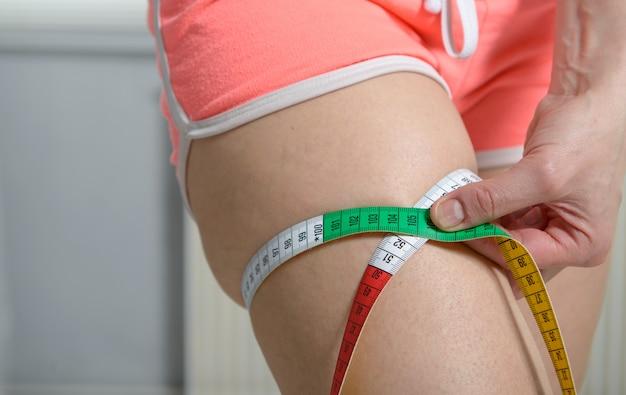 Szczupła młoda kobieta mierzy jej udo