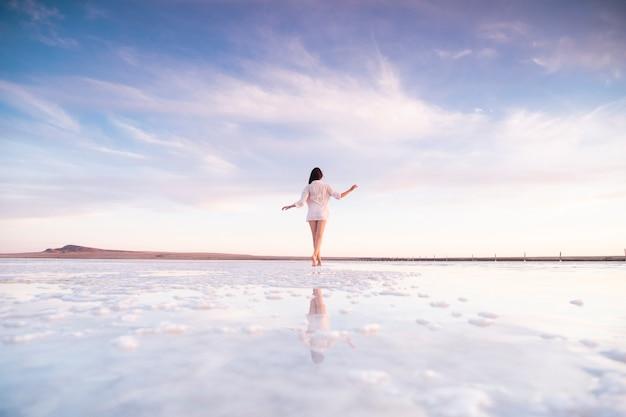 Szczupła młoda kobieta o zachodzie słońca od tyłu. dziewczyna spaceruje po słonym jeziorze. brunetka nad morzem.