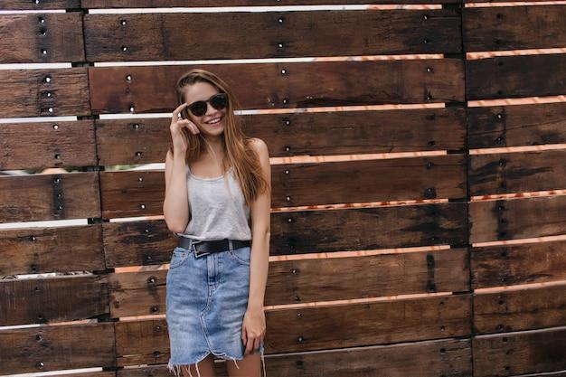 Szczupła młoda kobieta pozuje na drewnianej ścianie i dotyka jej okulary przeciwsłoneczne. plenerowy portret ekstatycznej kaukaskiej dziewczyny nosi dżinsową spódnicę.