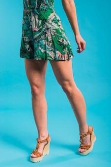 Szczupła młoda kobieta pozuje w kwitnącej sukni