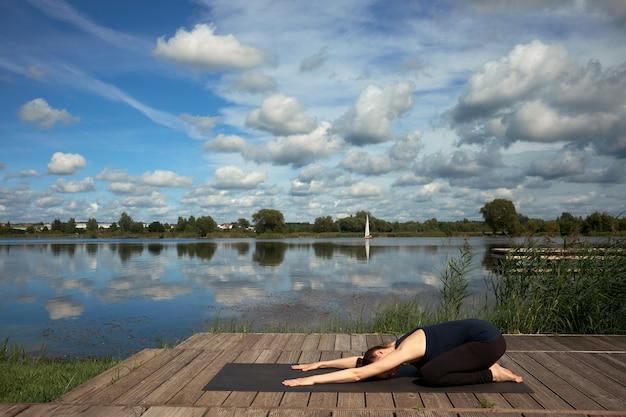 Szczupła młoda kobieta praktykuje jogę na drewnianym molo w pobliżu jeziora.