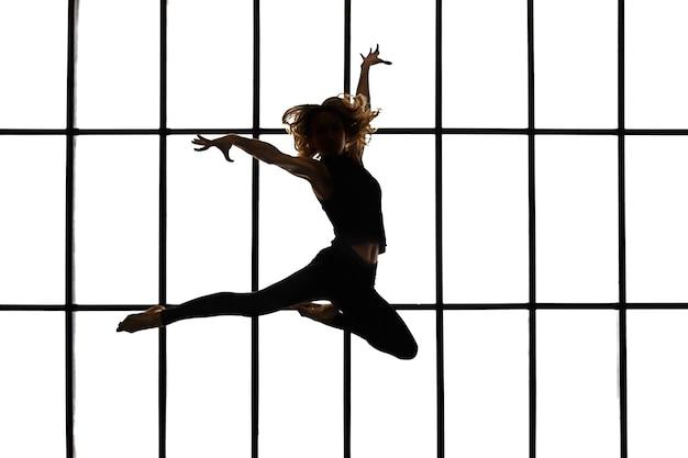 Szczupła młoda kobieta skacze na tle dużego okna. sylwetka. pojęcie zdrowego stylu życia i sportu.