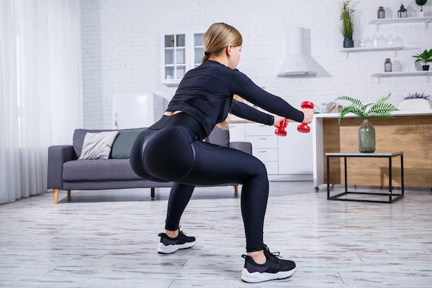 Szczupła młoda kobieta uprawia sport w domu w koszulce i legginsach. fitness w domu dla pięknego ciała. ćwiczenia z hantlami na kobiece ciało. zdrowy tryb życia.
