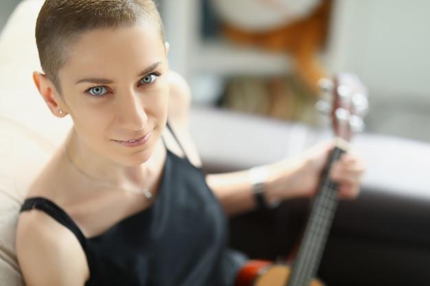 Szczupła młoda kobieta w czarnej sukience siedzi na kanapie i gra na musicalu ukulele