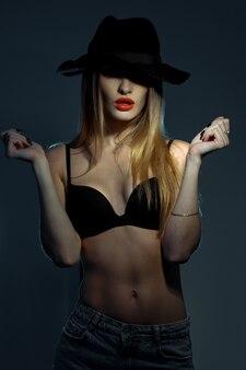 Szczupła młoda kobieta w czarnym biustonoszu z czerwonymi ustami w kapeluszu z szerokim rondem pozowanie