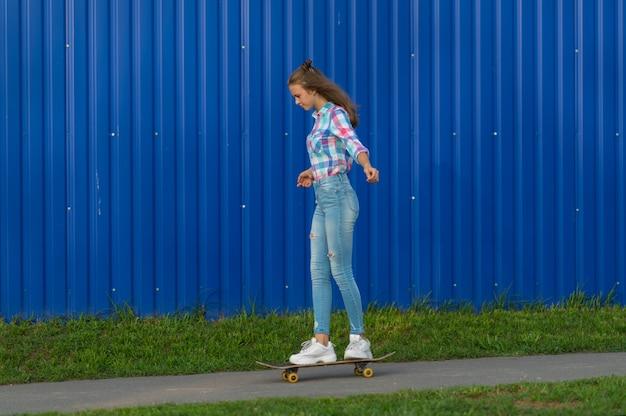Szczupła młoda kobieta w dżinsach jeździ na deskorolce wąską ścieżką w mieście przed kolorową niebieską ścianą