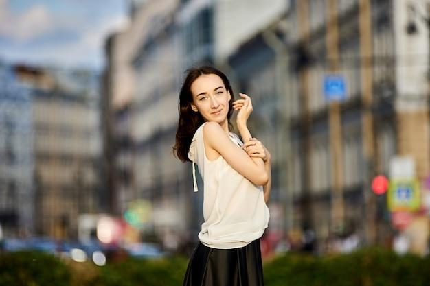 Szczupła młoda kobieta w wieku lat stoi na ulicy miasta