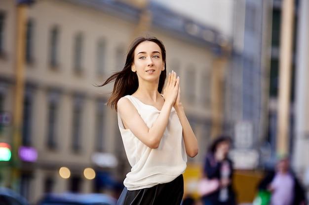 Szczupła młoda kobieta z czarnymi włosami spaceruje latem na świeżym powietrzu