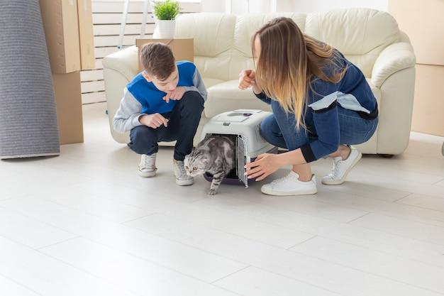 Szczupła, młoda matka i synek wprowadzają pięknego szarego kota szkockiego zwisającego do nowego