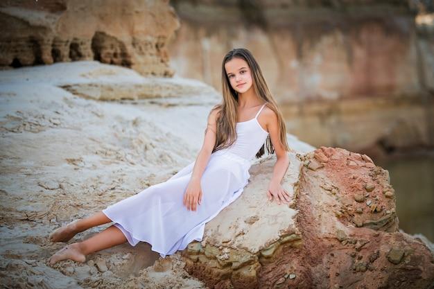 Szczupła nastolatka w białej sukience siedzi na piasku i wyciąga długie nogi
