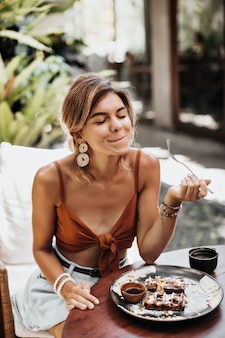 Szczupła opalona kobieta w brązowym staniku i stylowych dżinsowych szortach cieszy się smakiem gofra ze śmietaną, orzeszkami ziemnymi i syropem klonowym