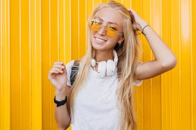 Szczupła, pełna wdzięku dziewczyna bawi się swoimi długimi blond włosami. spektakularna młoda kobieta w okularach przeciwsłonecznych i słuchawkach.