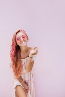 Szczupła piękna kobieta o długich różowych włosach z delikatnym uśmiechem.