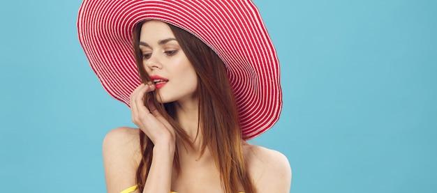 Szczupła piękna kobieta przygotowuje się do wakacji i zbiera walizkę, żółtą walizkę, kapelusz kostium kąpielowy, zdjęcie na wakacje