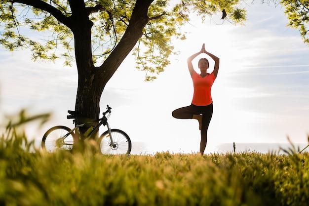 Szczupła, piękna kobieta sylwetka uprawiania sportu rano w parku robi joga