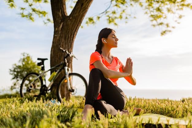 Szczupła piękna kobieta uprawiania sportu rano w parku robi joga