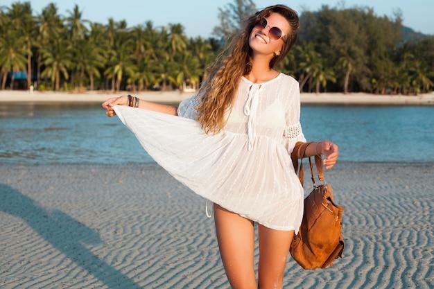 Szczupła piękna kobieta w białej sukni na tropikalnej plaży o zachodzie słońca, trzymając skórzany plecak.