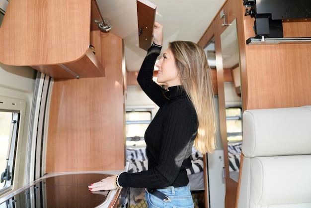 Szczupła piękna kobieta żyjąca w samochodzie kempingowym motor rv styl życia wnętrza domu w vanlife