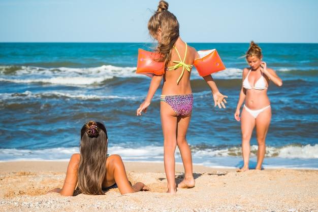 Szczupła, piękna młoda kobieta i dwie śliczne córeczki spędzają wakacje na piaszczystej plaży nad morzem w słoneczny letni dzień. koncepcja wakacji rodzinnych