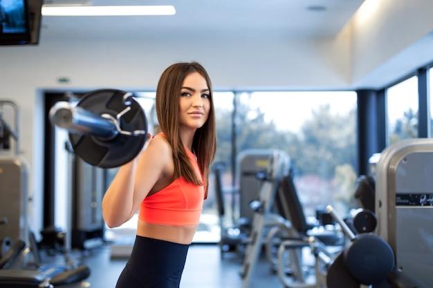 Szczupła przystojna młoda kobieta w kucki sportowej ze sztangą na ramieniu w siłowni