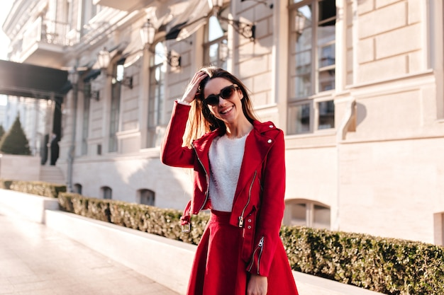 Szczupła roześmiana dziewczyna w dużych okularach przeciwsłonecznych, uśmiechając się, pozując w pobliżu starego budynku