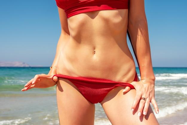 Szczupła seksowna dziewczyna o idealnej figurze w czerwonym bikini na plaży.