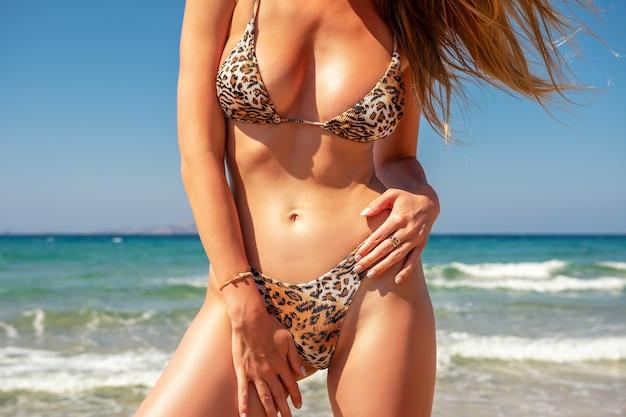 Szczupła seksowna dziewczyna o idealnej figurze w lampartowym bikini na plaży.