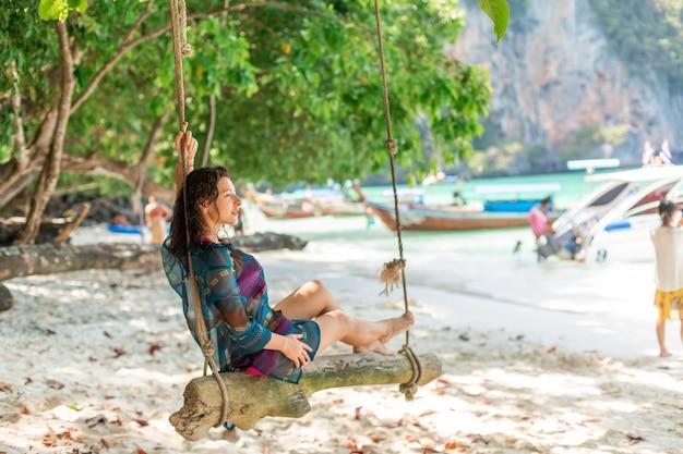 Szczupła seksowna modelka w stroju kąpielowym pozowanie na drewnianej huśtawce przywiązanej do drzewa.