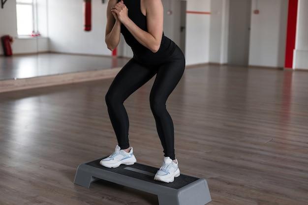 Szczupła, sportowa młoda kobieta w sportowych czarnych ubraniach kuca, stojąc na schodach platformy w siłowni
