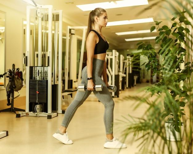 Szczupła sprawna kobieta w odzieży sportowej rzuca się z nogami z hantlami w dłoniach w sali gimnastycznej. koncepcja zdrowego stylu życia
