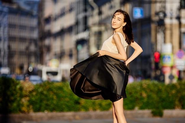 Szczupła szczęśliwa dziewczyna stoi w centrum miasta podczas spaceru