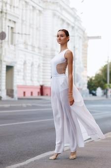 Szczupła tancerka w długiej białej sukni w mieście o świcie.