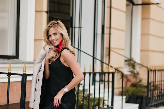Szczupła, zadowolona kobieta w modnym białym zegarku, śmiejąca się, pozując obok sklepu