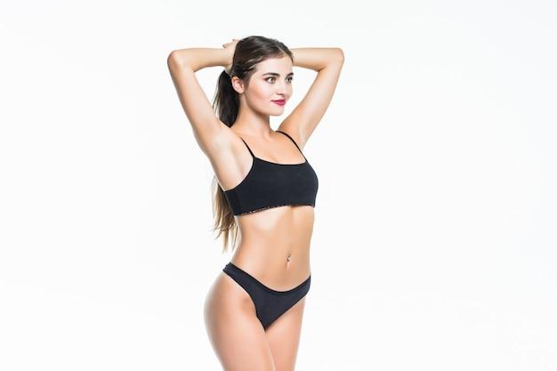 Szczupłe ciało młodej kobiety w czarnym bikini. dziewczyna z zdrowy sportowy rysunek na białej ścianie