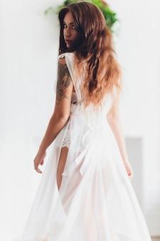 Szczupłe ciało opalonej kobiety na szarym tle