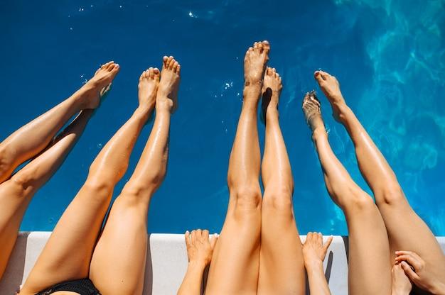Szczupłe kobiece nogi na basenie w ośrodku, widok z góry. piękne dziewczyny relaksują się przy basenie w słoneczny dzień, letnie wakacje atrakcyjnych dziewczyngirlfriend