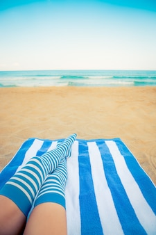 Szczupłe nogi kobiety na plaży. letnie wakacje i koncepcja podróży